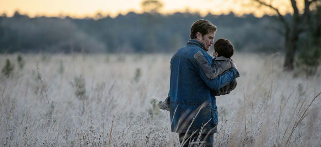 Entretien avec Jeff Nichols : scène où le père (Michael Shannon) porte l'enfant (Jaeden Lieberher) dans un champs - Midnight Special