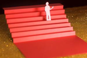 Cannes Sixième Jour les marches, escalier rouge en papier sur fons paillettes dorées