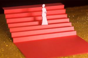 Cannes Troisième Jour les marches, escalier rouge en papier sur fons paillettes dorées